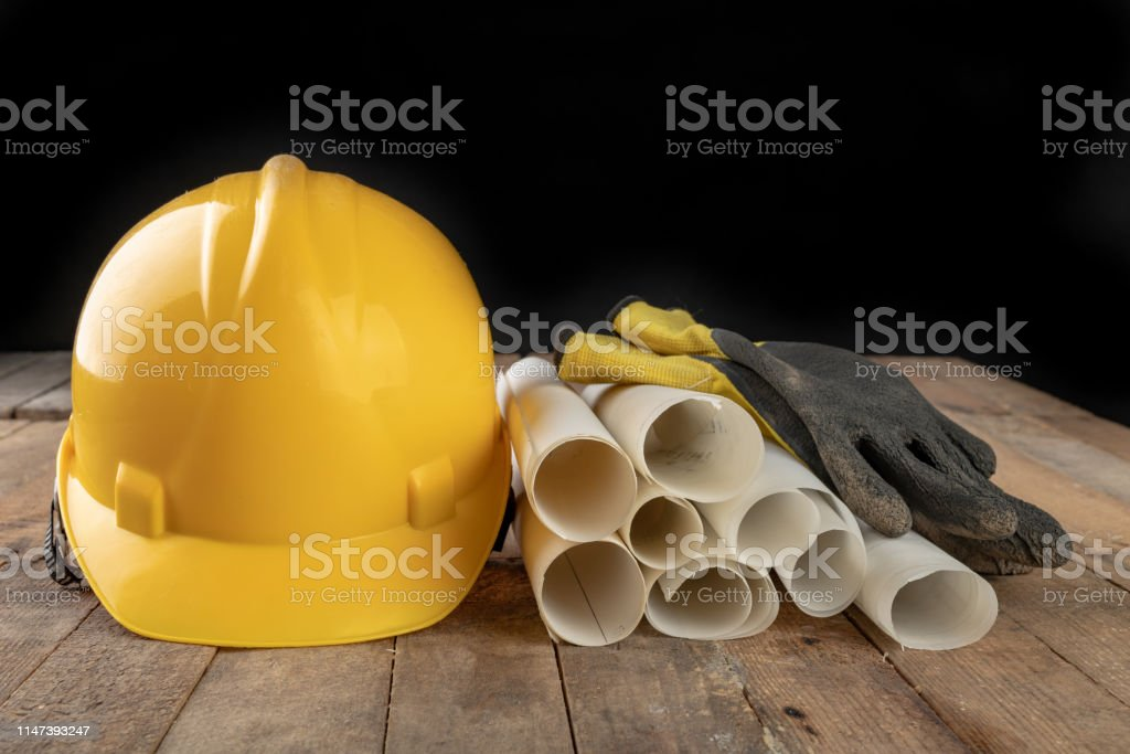 Construction helmet and roll of parchment with design. Construction...