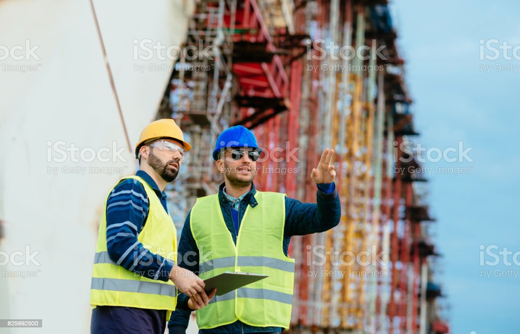 Engineers and architects on construction site, with blueprints and...