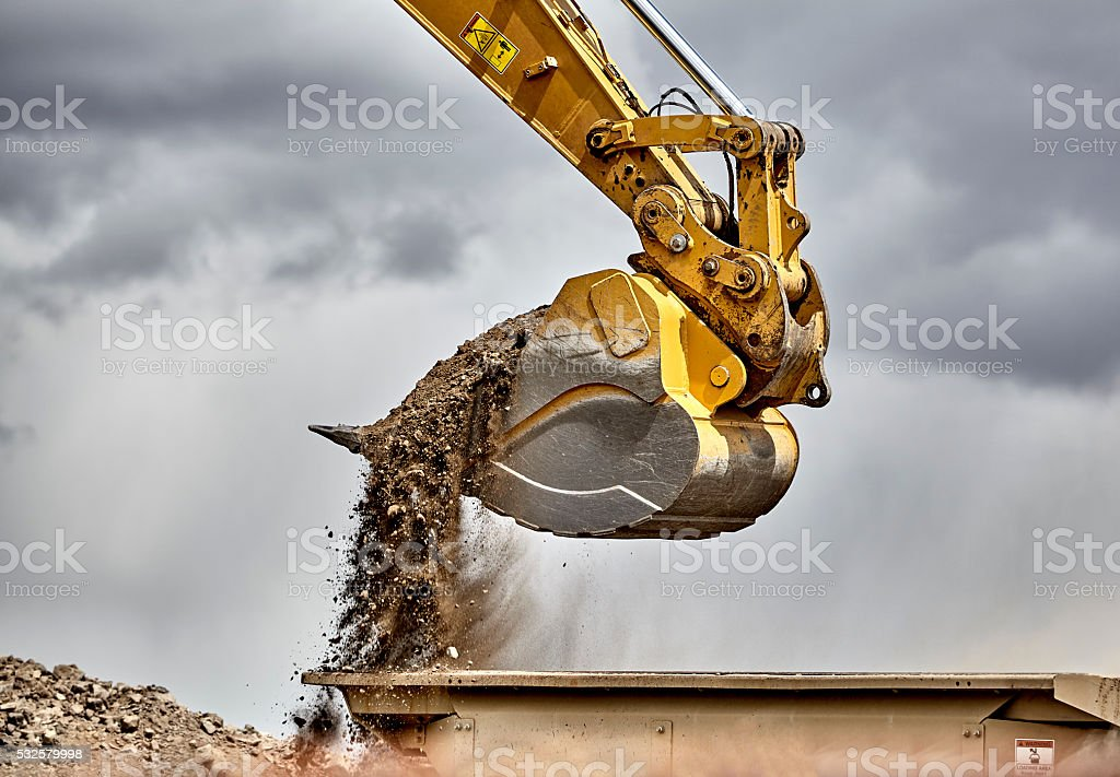 Construction industry excavator bucket loading gravel closeup stock photo