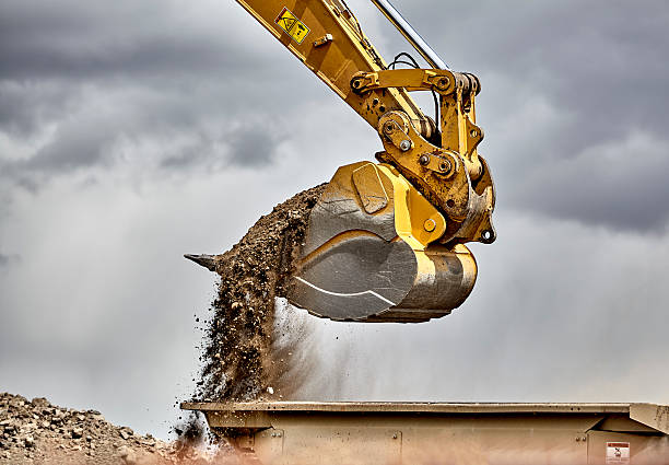 Construction industry excavator bucket loading gravel closeup Construction industry heavy equipment excavator moving gravel at jobsite quarry with stormy skies construction machinery stock pictures, royalty-free photos & images