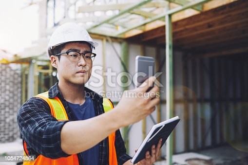 1054724700istockphoto Construction industry measuring with smart phone application. 1054724864