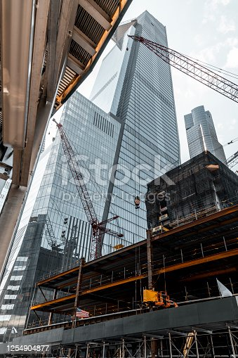 Construction of a modern office building, tall modern skyscraper in the background, New York.