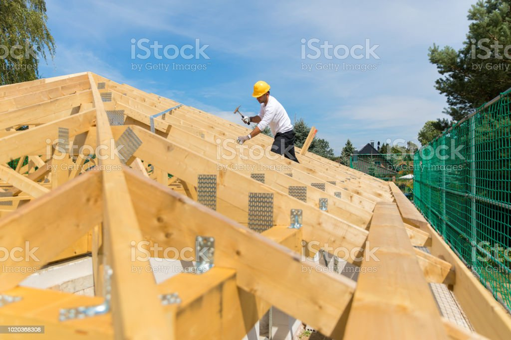 Construction Industry - Roofer carpenter working on roof stock photo