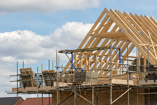 Construction industry. Timber framework of house roof trusses with scaffold on a building being built on a new housing estate.