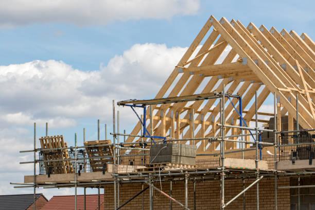 industria edile. struttura in legno di capriate del tetto della casa con impalcatura. - costruire foto e immagini stock