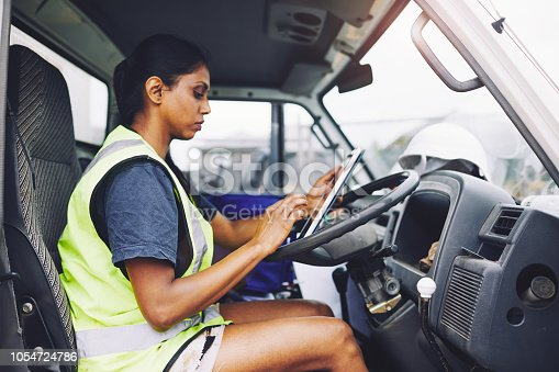 1054724700istockphoto Construction industry worker texting on the digital tablet inside a truck. 1054724786