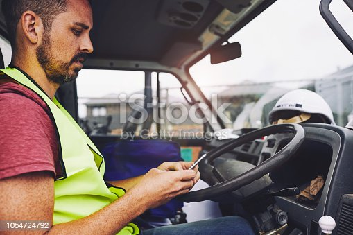 SydneyConstruction. Construction industry worker texting on the phone inside a truck.
