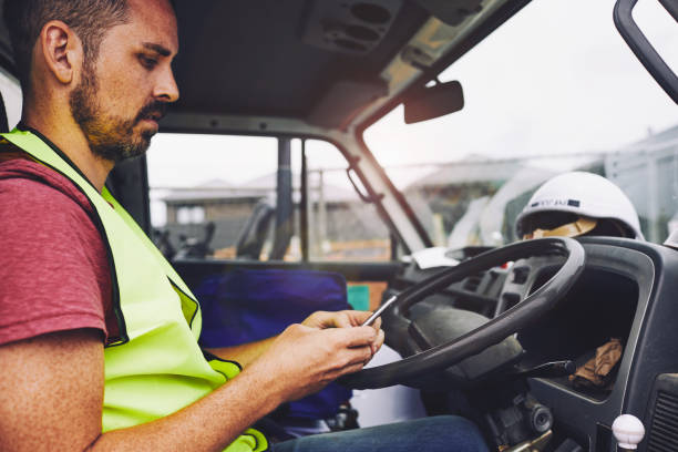 Construction industry worker texting on the phone inside a truck. SydneyConstruction. Construction industry worker texting on the phone inside a truck. commercial land vehicle stock pictures, royalty-free photos & images