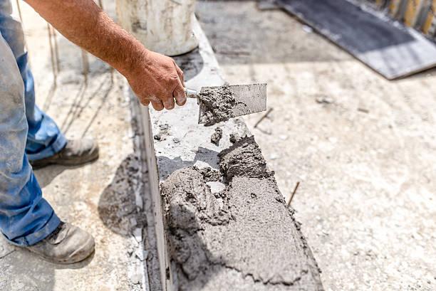 bau-industrie arbeiter mit einem kitt messer und powerleveling konkrete - betonwerkstein stock-fotos und bilder