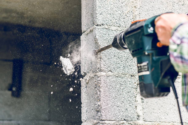 Construction industry worker using pneumatic hammer drill to cut the wall concrete brick, close up Construction industry worker using pneumatic hammer drill to cut the wall concrete brick, close up drill stock pictures, royalty-free photos & images