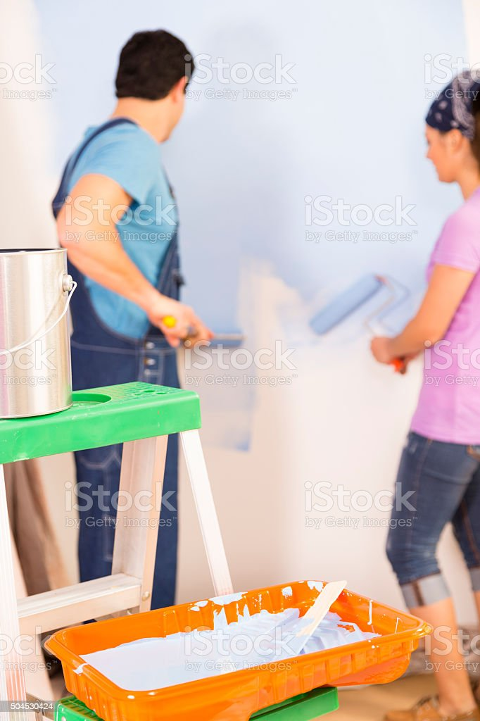 Construction: Latin couple remodeling their home. Painting wall. stock photo