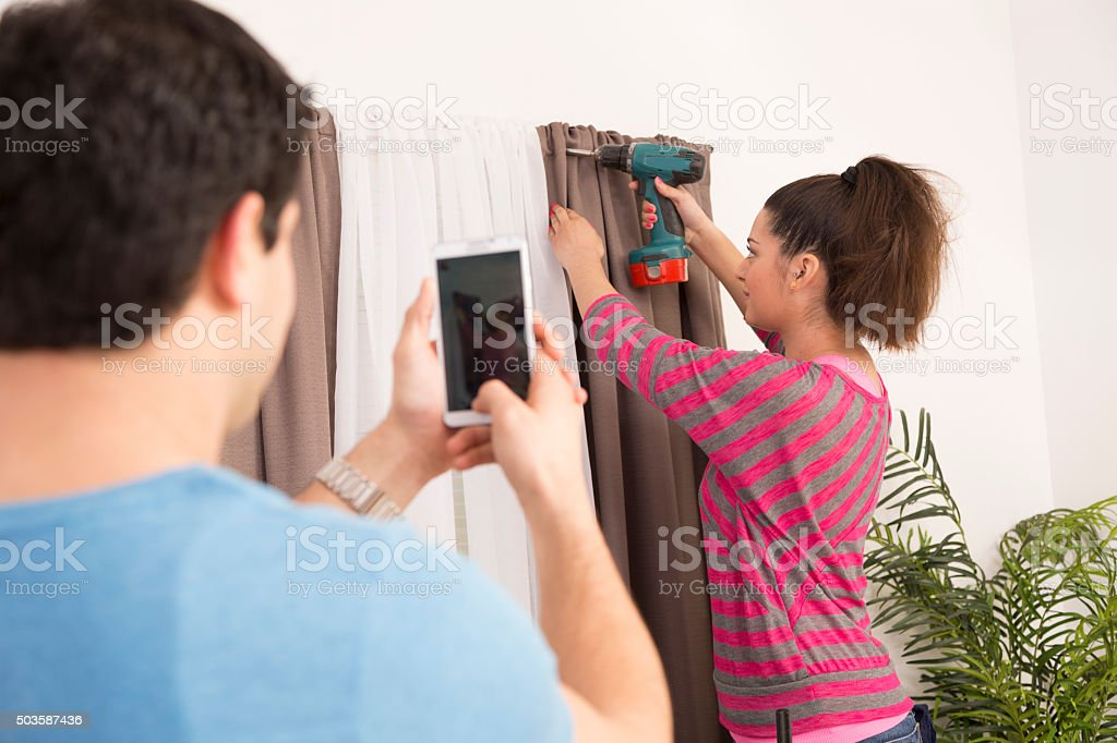 Construction: Latin couple work together on home improvement projects. Photographing. stock photo