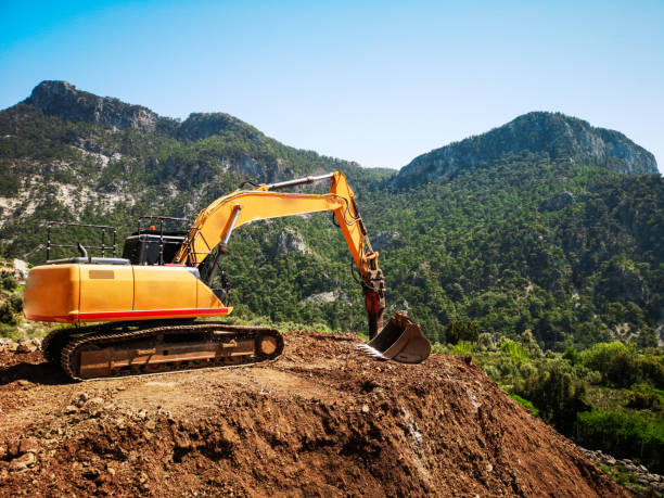 Construction machine destructing the natural land stock photo