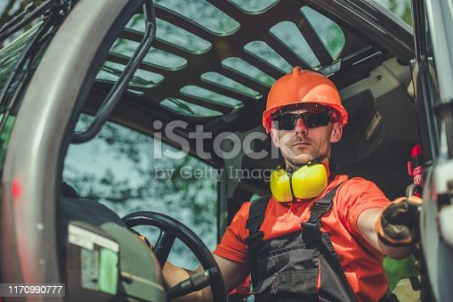 Construction Machine Operator. Caucasian Worker Inside Modern Industrial Machinery.