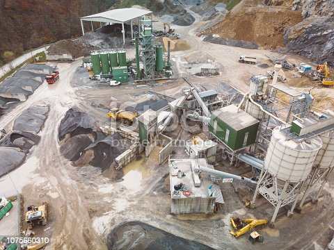 At a quarry worksite. Aerial footage, shoot with drone, open-pit quarry, in which stone, rock, sand or gravel is excavated from the ground. There are bulldozers, tipper and other construction trucks driving on the ground.