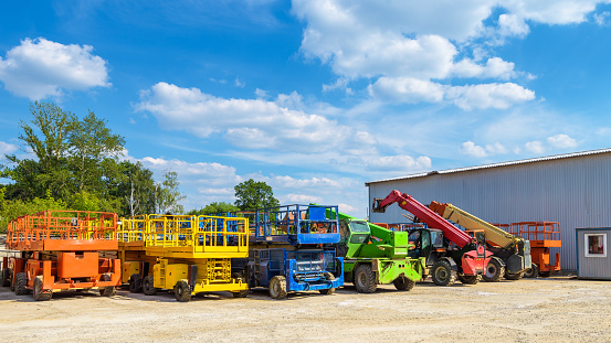 Construction machinery in summer. Colorful vehicles and heavy trucks on the outdoor parking. Panorama of the repair equipment on sunny day. Cherry pickers in folded form.