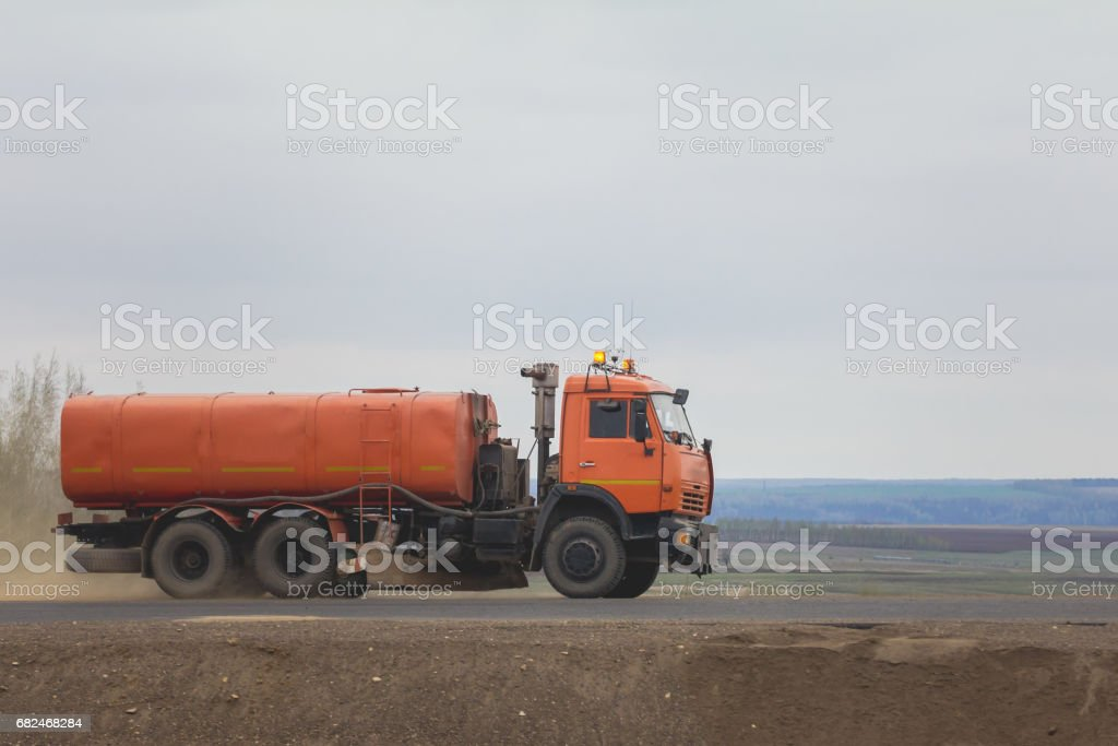 Construction machinery - watering truck at highway among field royalty free stockfoto