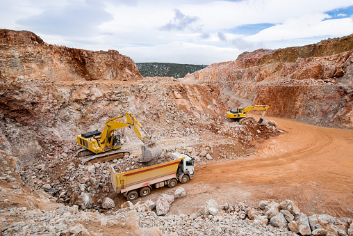 Excavators are loading dumper truck in a quarry.