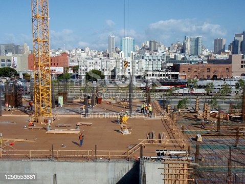 San Francisco - April 29, 2008: Construction machines and people works at High-rise Construction site in San Francisco with Caltrain and great skyline in the distance.