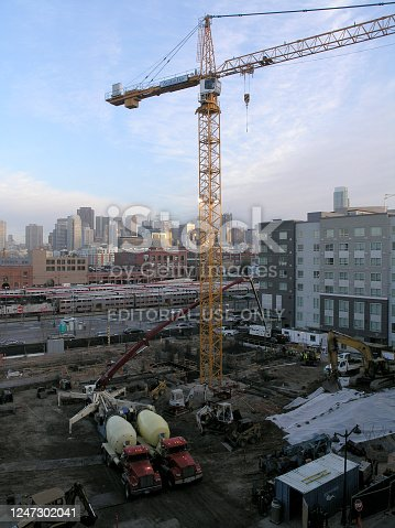 San Francisco - March 7, 2008: Construction machines, Cranes,  and Cement trucks works at High-rise Construction site in San Francisco with Caltrain and great skyline in the distance.