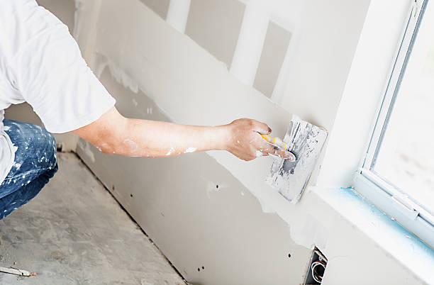 Construction: Man installing plasterboard Man spackling new drywall or plasterboard plaster stock pictures, royalty-free photos & images