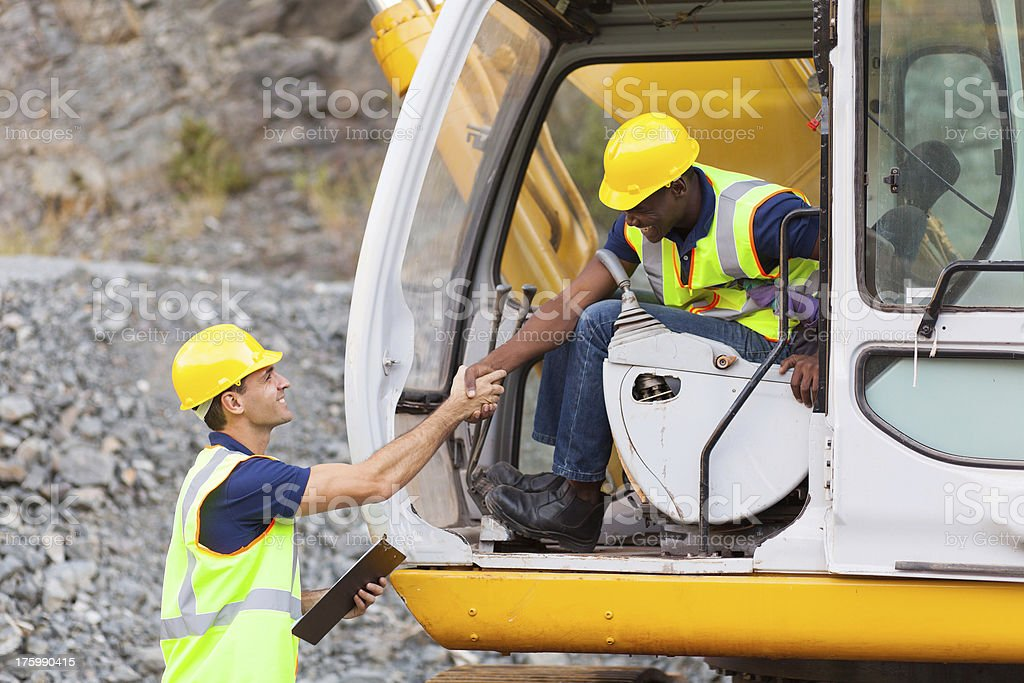 construction manager handshaking with bulldozer operator stock photo