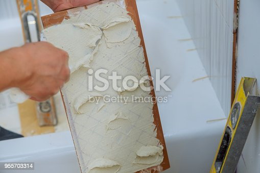 1138442636 istock photo construction mason man hands on tiles work with cement mortar 955703314