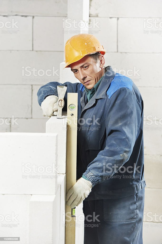 construction mason worker bricklayer with level royalty-free stock photo