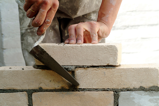 Construction worker laying bricks in a construction site.