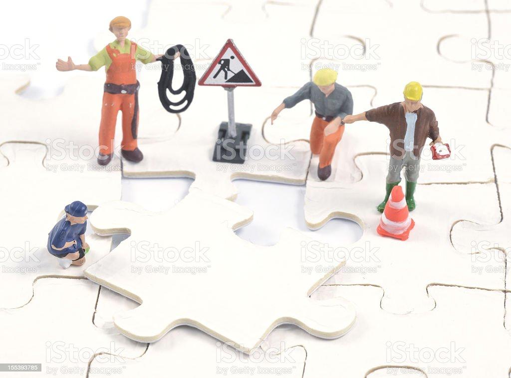 construction men build on last puzzle piece stock photo
