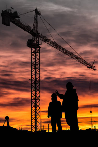 Construction Mentor Powerful silhouette of 2 workers discussing the job with a tower crane in the background. rigging stock pictures, royalty-free photos & images