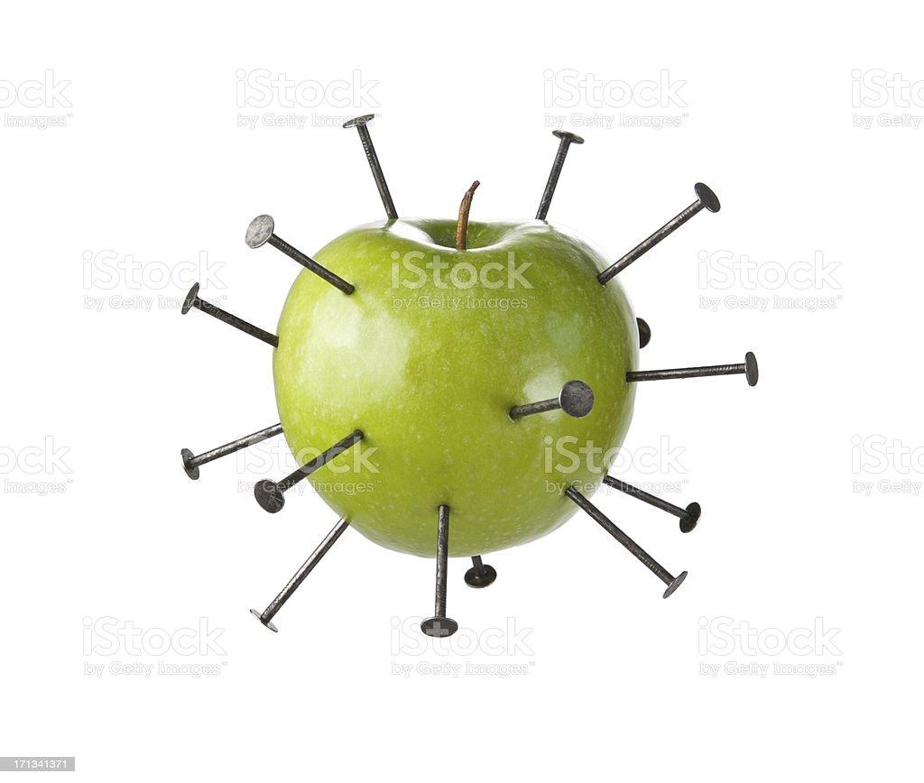 Construction nails piercing a green apple - Royaltyfri Bisarr Bildbanksbilder