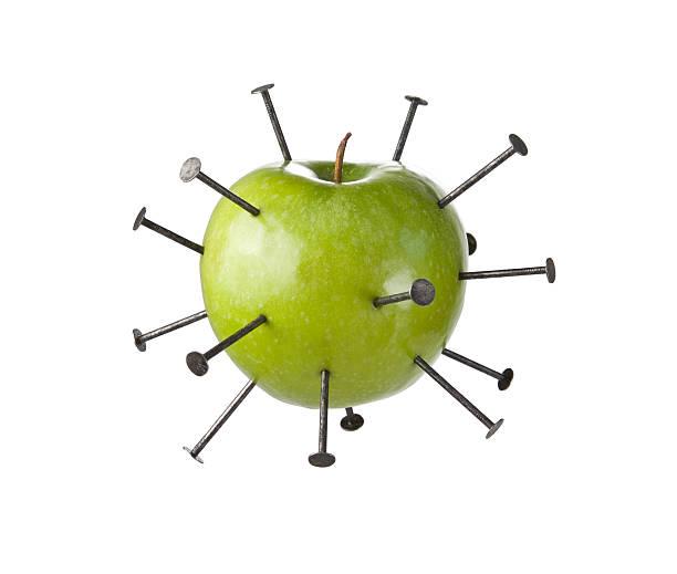 construction nails piercing a green apple - penetrating bildbanksfoton och bilder