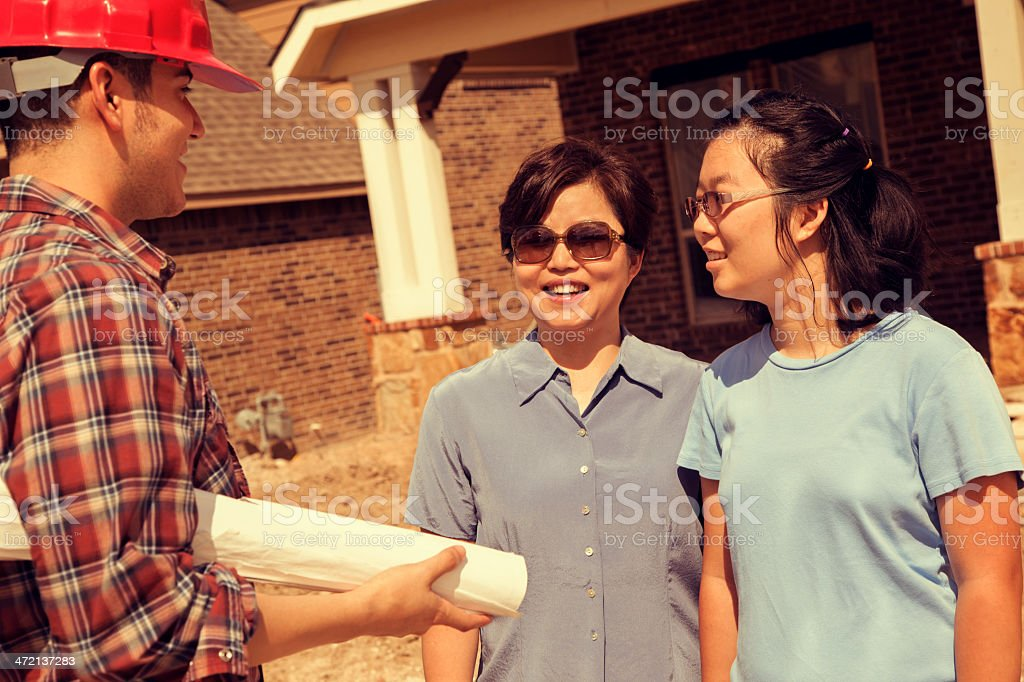 Asian mother and daughter new home buyers discuss house construction...