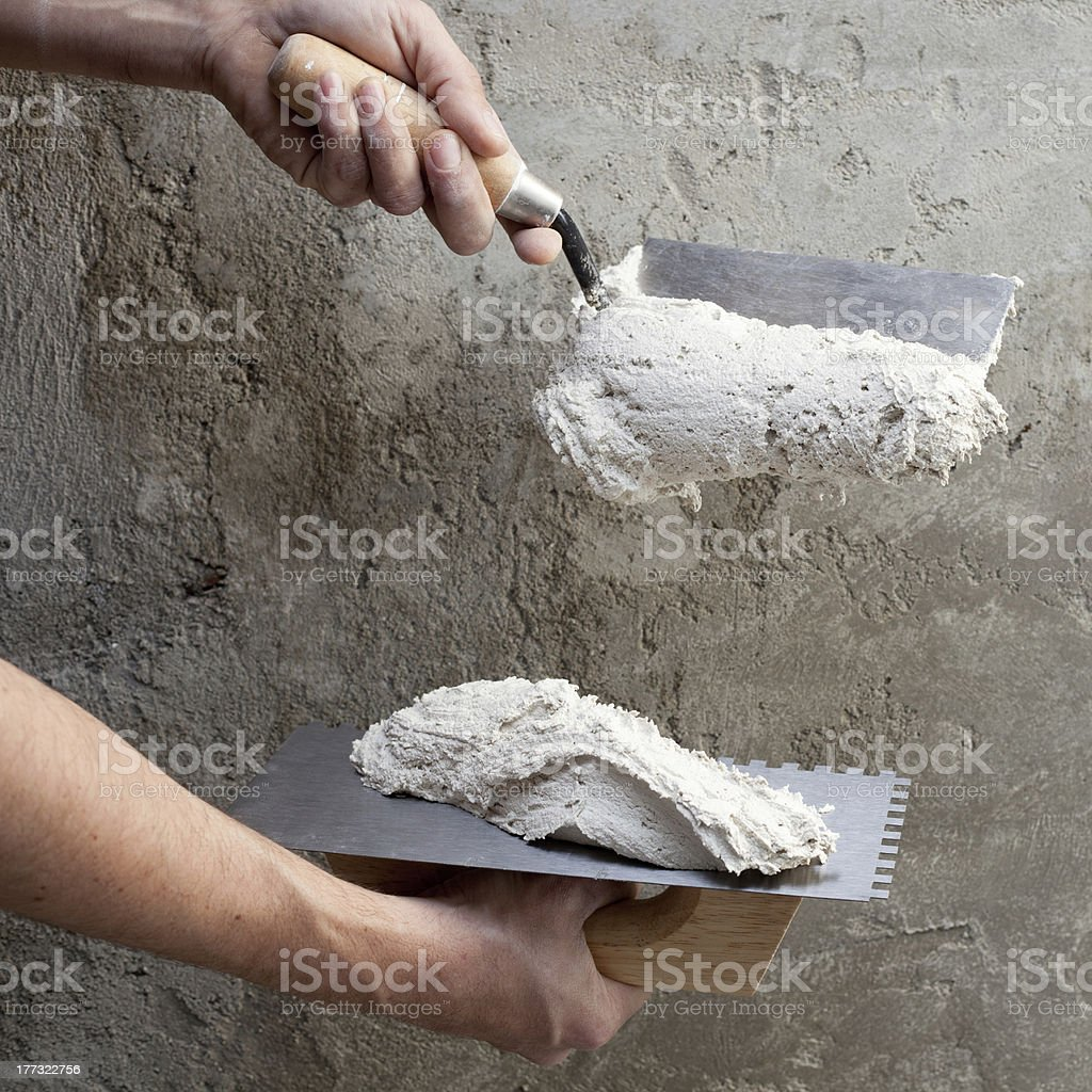 construction notched trowel and worker hands stock photo