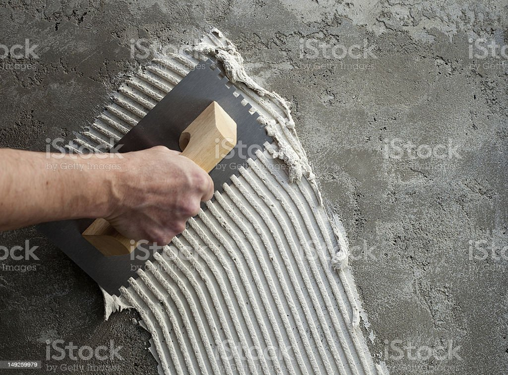 construction notched trowel with white cement stock photo