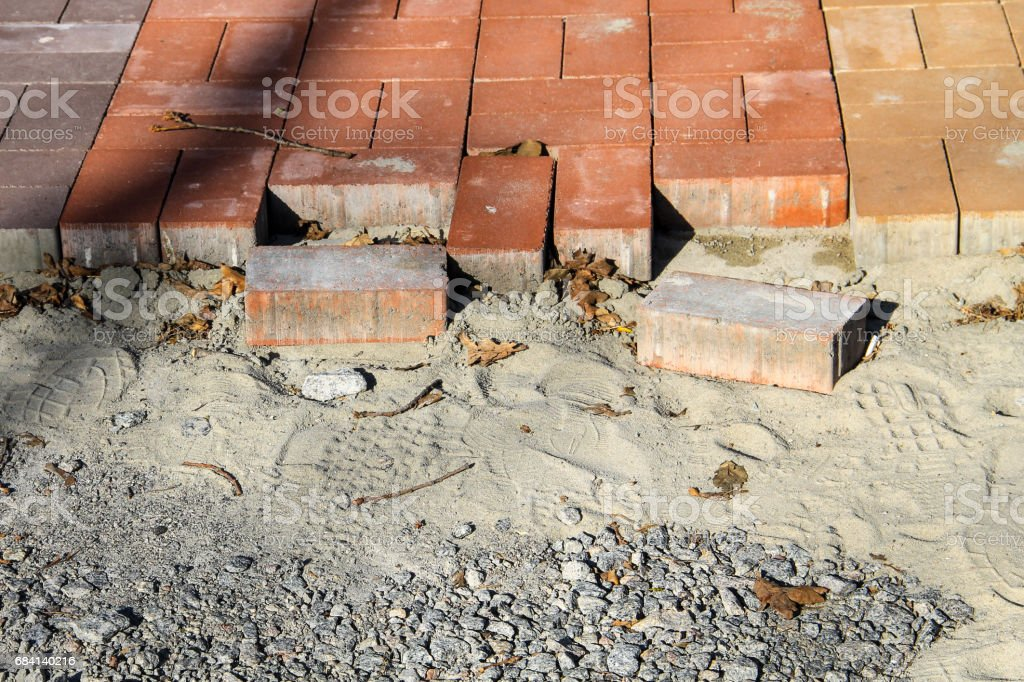 Construction of a new pavement of paving slabs. Pavement cobblestone blocks construction of path, road or sidewalk foto stock royalty-free