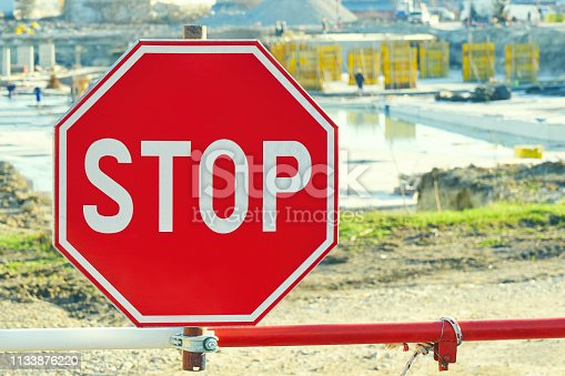 istock Construction of a resort hotel. Restrictive stop sign close-up. Builders at work on a sunny day 1133876220