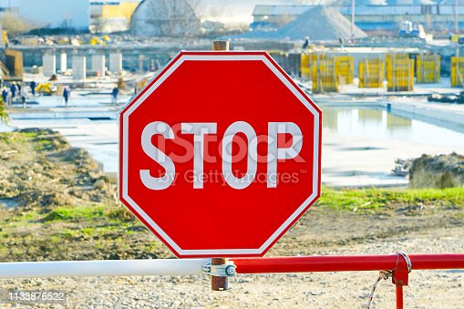 istock Construction of a resort hotel. Restrictive stop sign close-up. Builders at work on a sunny day 1133876522