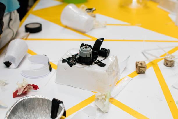 bau eines roboters aus abfallmaterialien. stammen sie aktivitäten für kinder auf technik, elektronik, robotik und kreislaufwirtschaft. - roboter bastelarbeiten stock-fotos und bilder