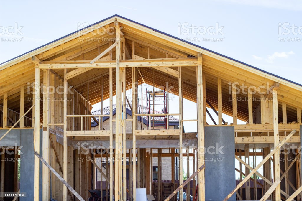 Construction of a wooden house. Beam. Blue Sky. Architecture