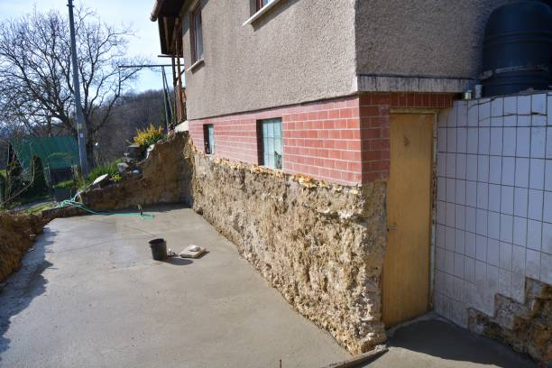 Construction of foundations next to the wall of the existing cottage stock photo