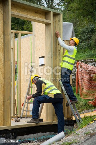 Manual workers working with construction frame at construction site.