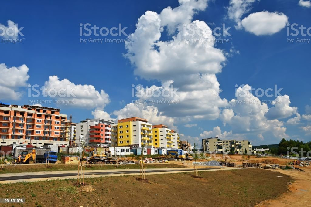 Construction of new homes. Concept for industry. Crane and blue sky with clouds and sun. Building construction site at sunset royalty-free stock photo
