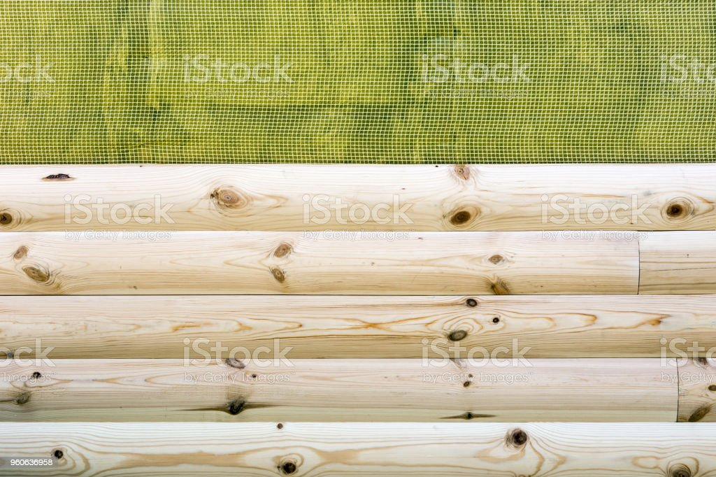 Construction of new house building. Installation of wooden siding wall covering over waterproofing membrane outdoor stock photo
