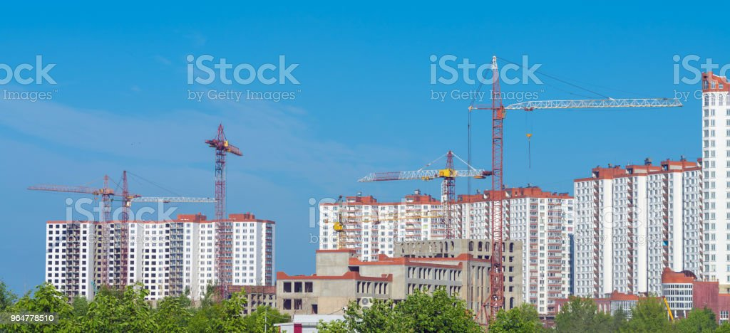 Construction of new multi-storey buildings with the help of cranes. Panoramic view of the building. royalty-free stock photo