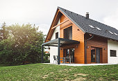 Customized wooden holiday villa, nature friendly mateirals, black roof, wooden facade, minimalistic architecture, beautiful backyard perfect for picnics, holiday villa for the upper class, perfect for a weekend off.