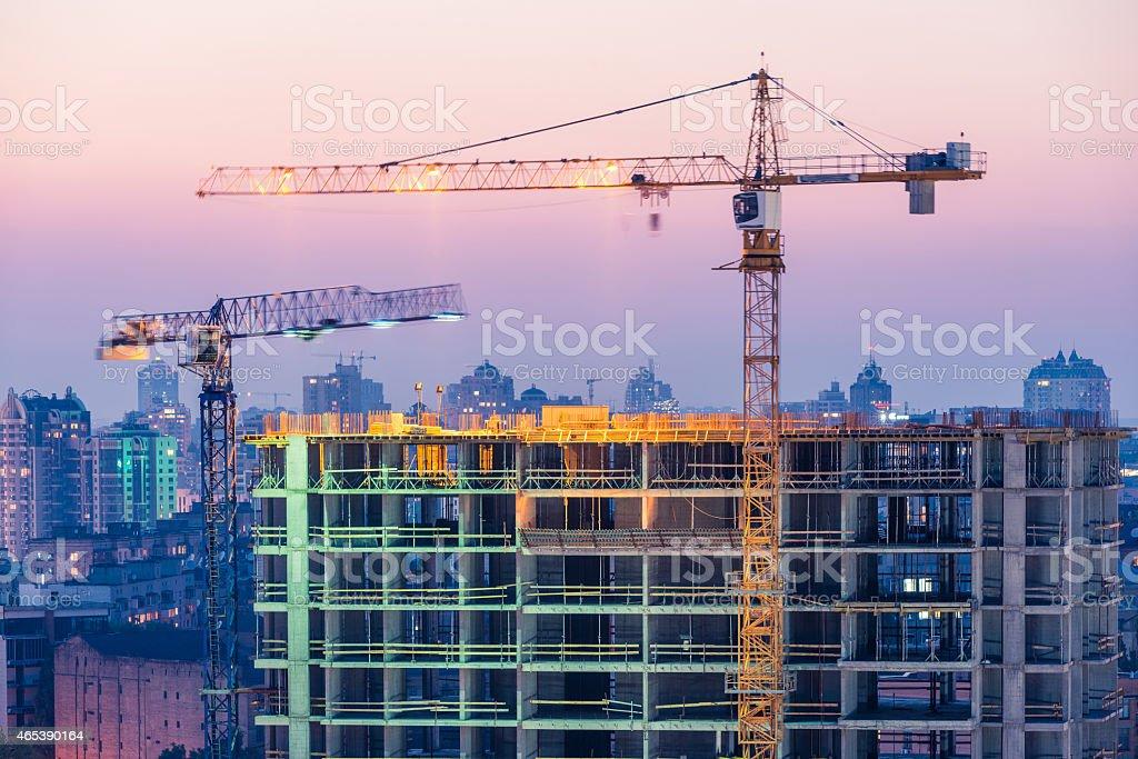 Bau von Bürogebäude auf Lila Sonnenuntergang mit zwei cranes – Foto