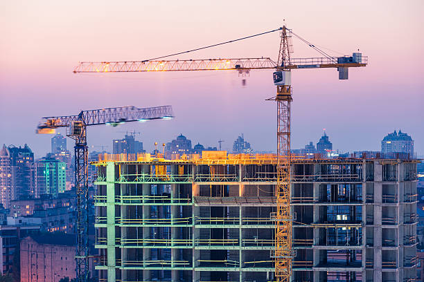 Construction of office building on purple sunset with two cranes stock photo