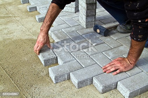 Construction of pavement. Worker puts paving